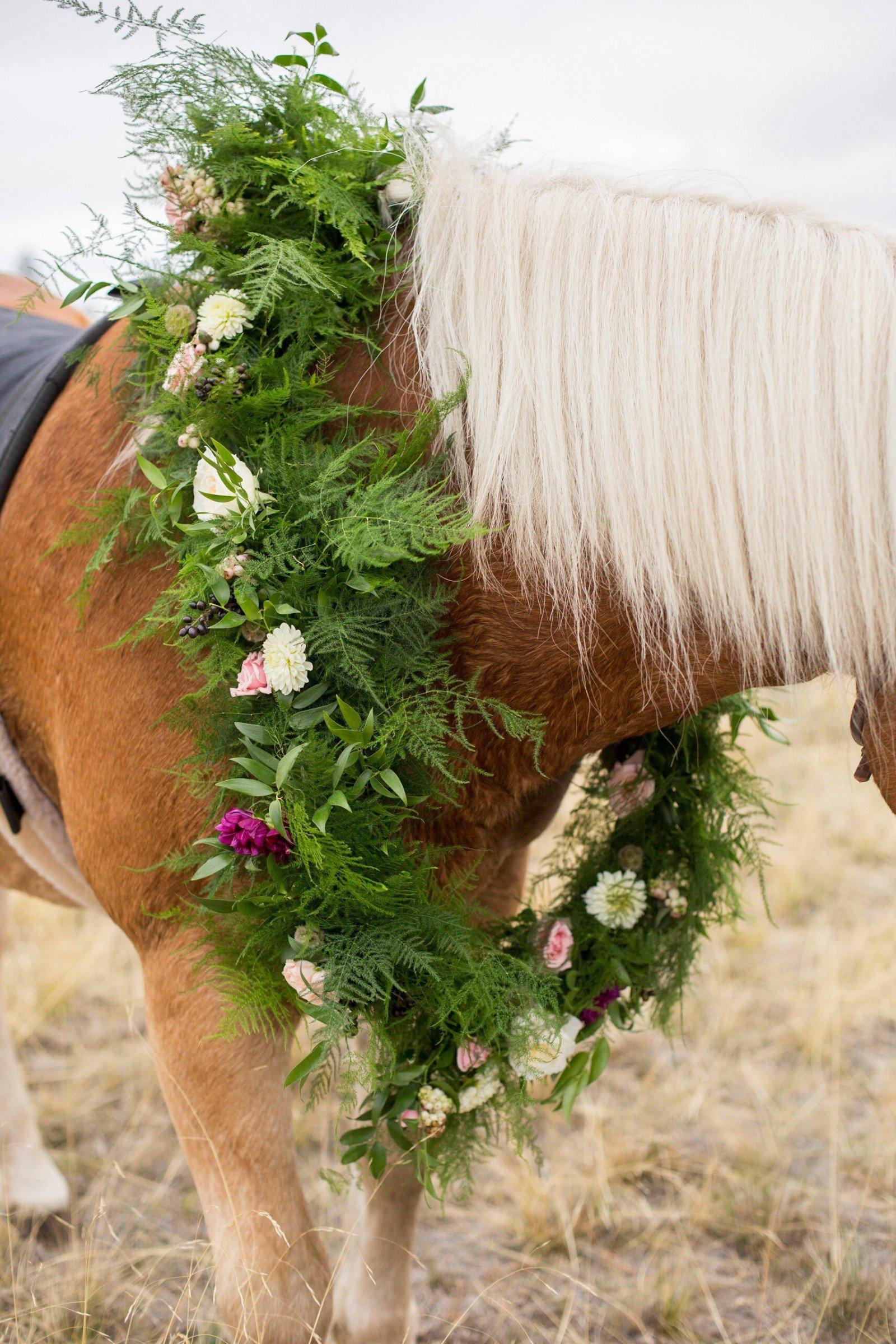 A bespoke floral garland adorns a horse at a destination wedding at The Ranch at Rock Creek