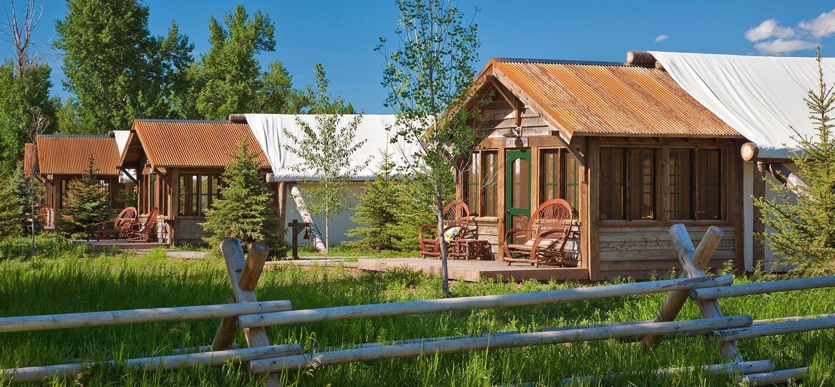宿泊エリアの外観。木を基調とした建物とテントのタープが印象的