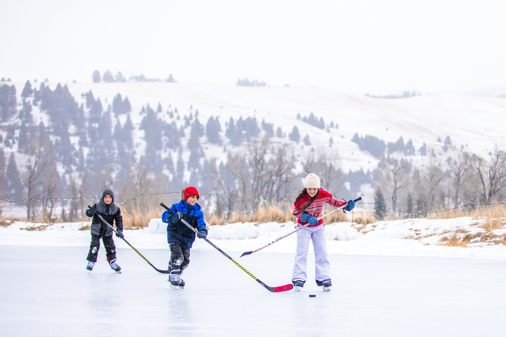 three kids play hockey on the ice at The Ranch at Rock Creek