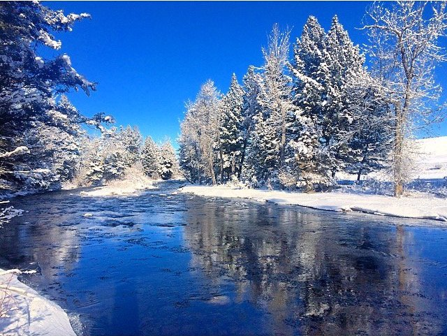 Rock Creek's beautiful water reflects the Big Sky and the snow covered trees
