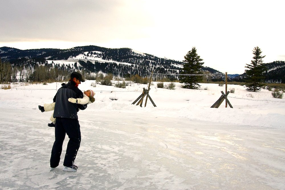 A father skates with his daughter on the Granite Lodge pond at The Ranch at Rock Creek