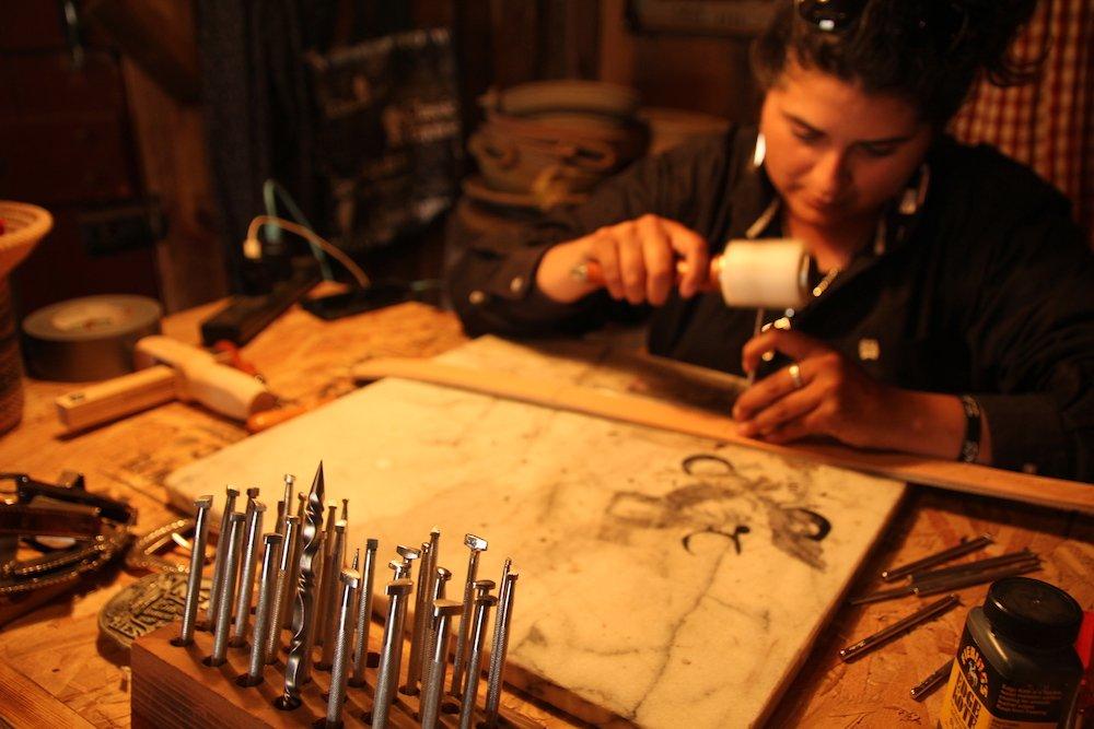 Lead wrangler and artisan Mindy Avila creates a custom-tooled belt in her studio