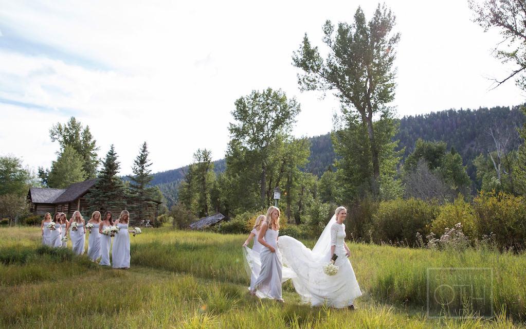 A bride walks near Rock Creek during a glamping inspired wedding