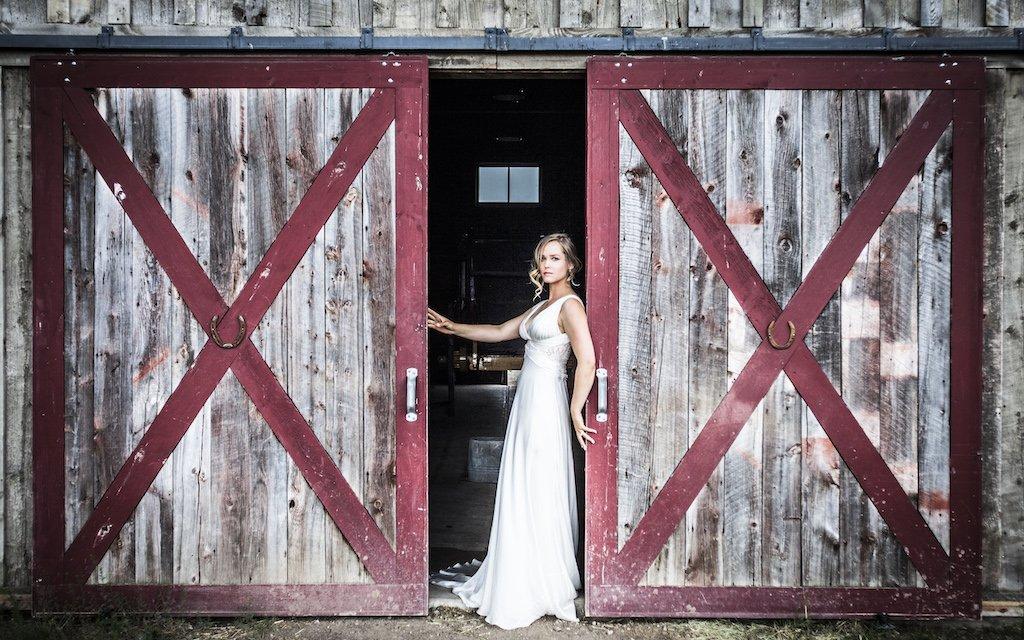 A traditional Montana barn makes the perfect backdrop for a bride's wedding photos