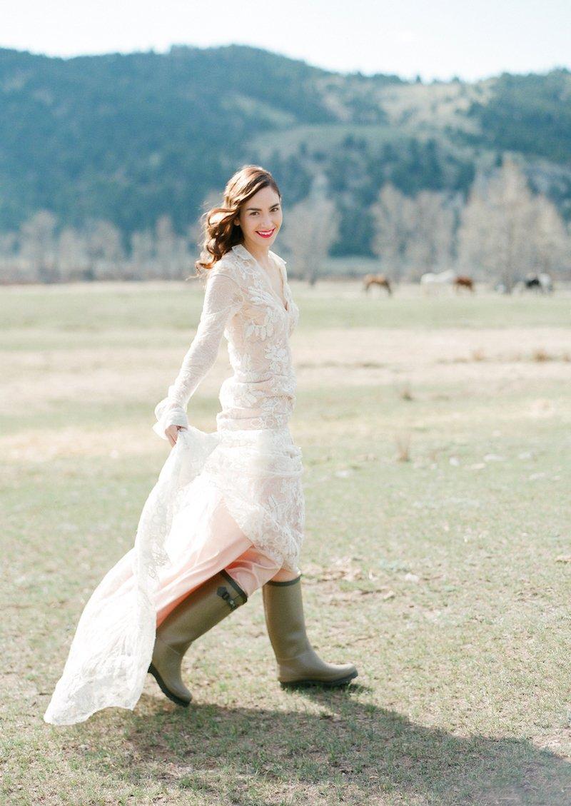 A bride walks across a Montana pasture in rain boots during a spring wedding shoot