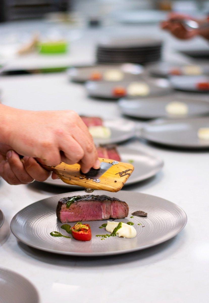chef grates truffles onto a tasting menu plate