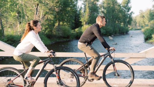 Guests ride mountain bikes over Rock Creek bridge