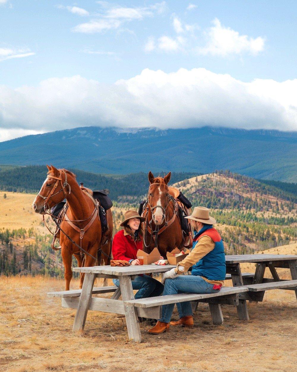 A couple enjoy a mountaintop lunch during a horseback riding excursion at Montana's Ranch at Rock Creek