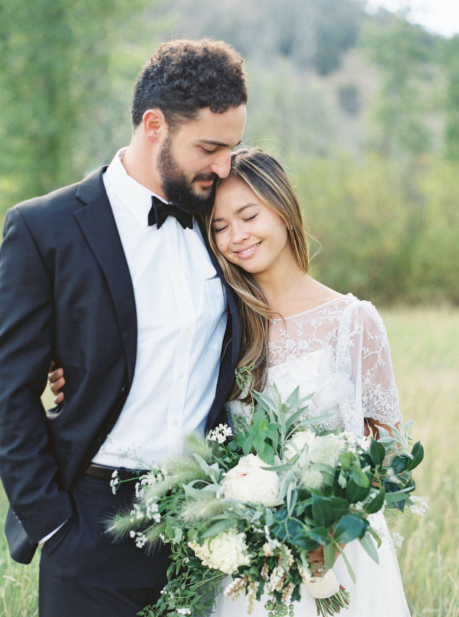 A bride rests her head against her groom's shoulder after a ranch elopement