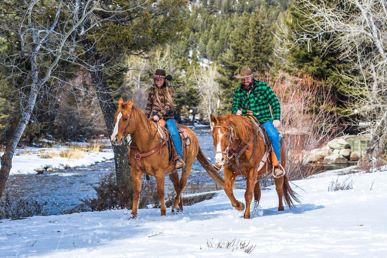 A couple takes a horseback ride through the snow at The Ranch at Rock Creek